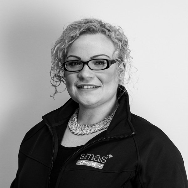 Hollie Baxter, Client Relations Manager of SMAS Worksafe smiles for her company profile picture wearing a black SMAS Worksafe jacket and necklace
