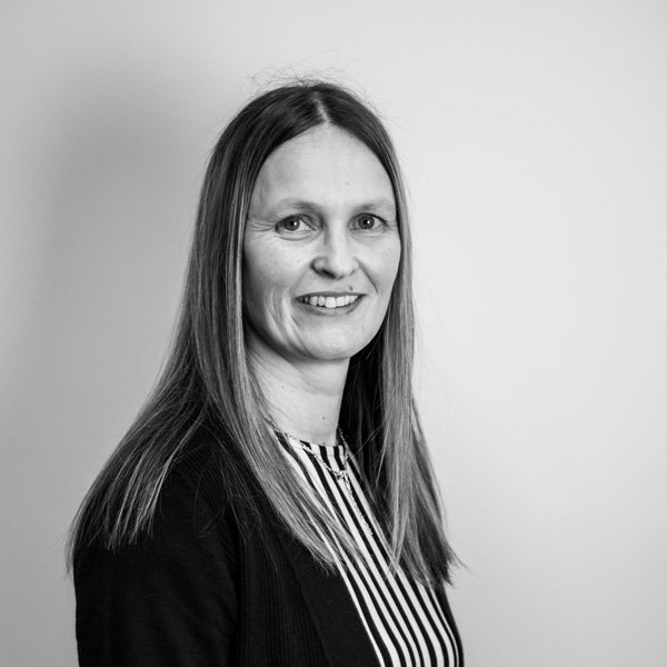 Nicole Bleasdale, Operational Support Manager poses for her professional profile picture in a black and white stripped top and black cardigan